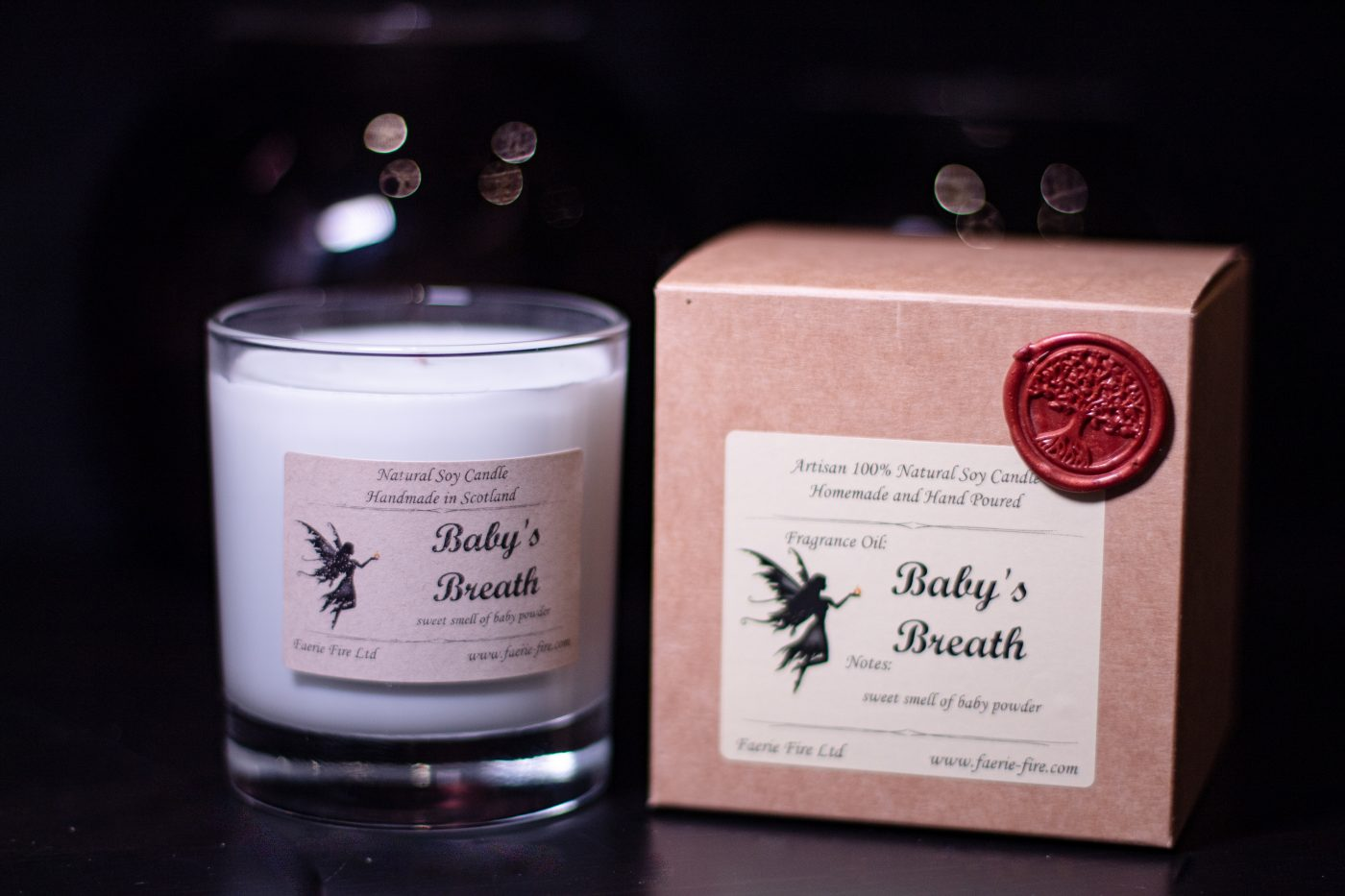 Image of very pale blue baby powder fragranced jar candle with a brown kraft box on a table with a dark background