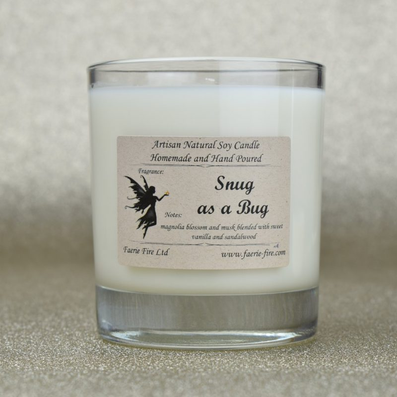 Snug as a bug magnolia fragranced white soy candle in a clear glass jar against a gold background