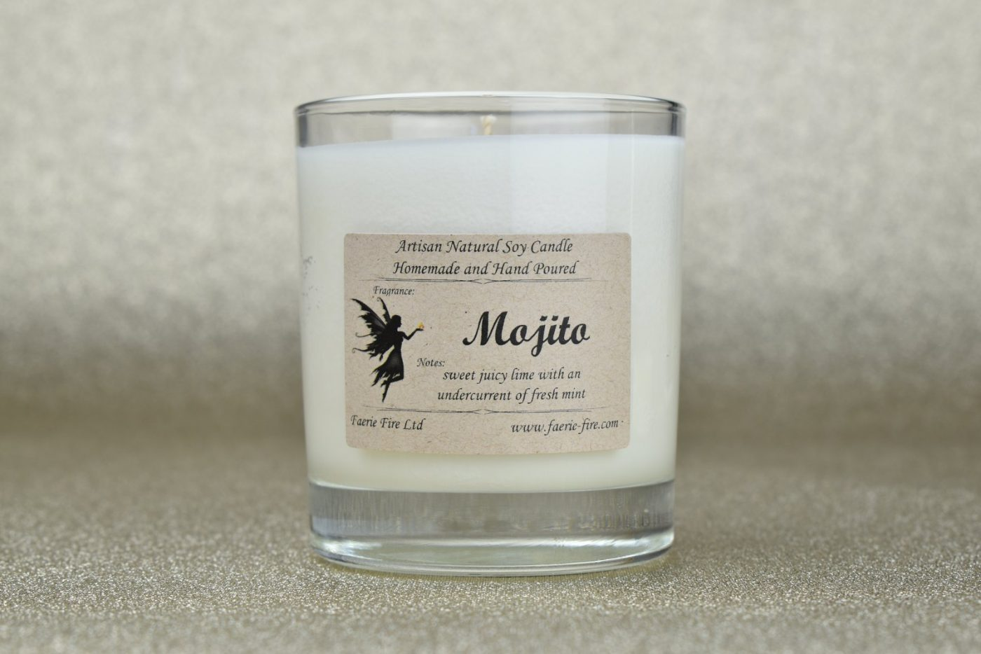 White soy Mojito candle in a clear glass smilling like lime and mint against a pale gold background