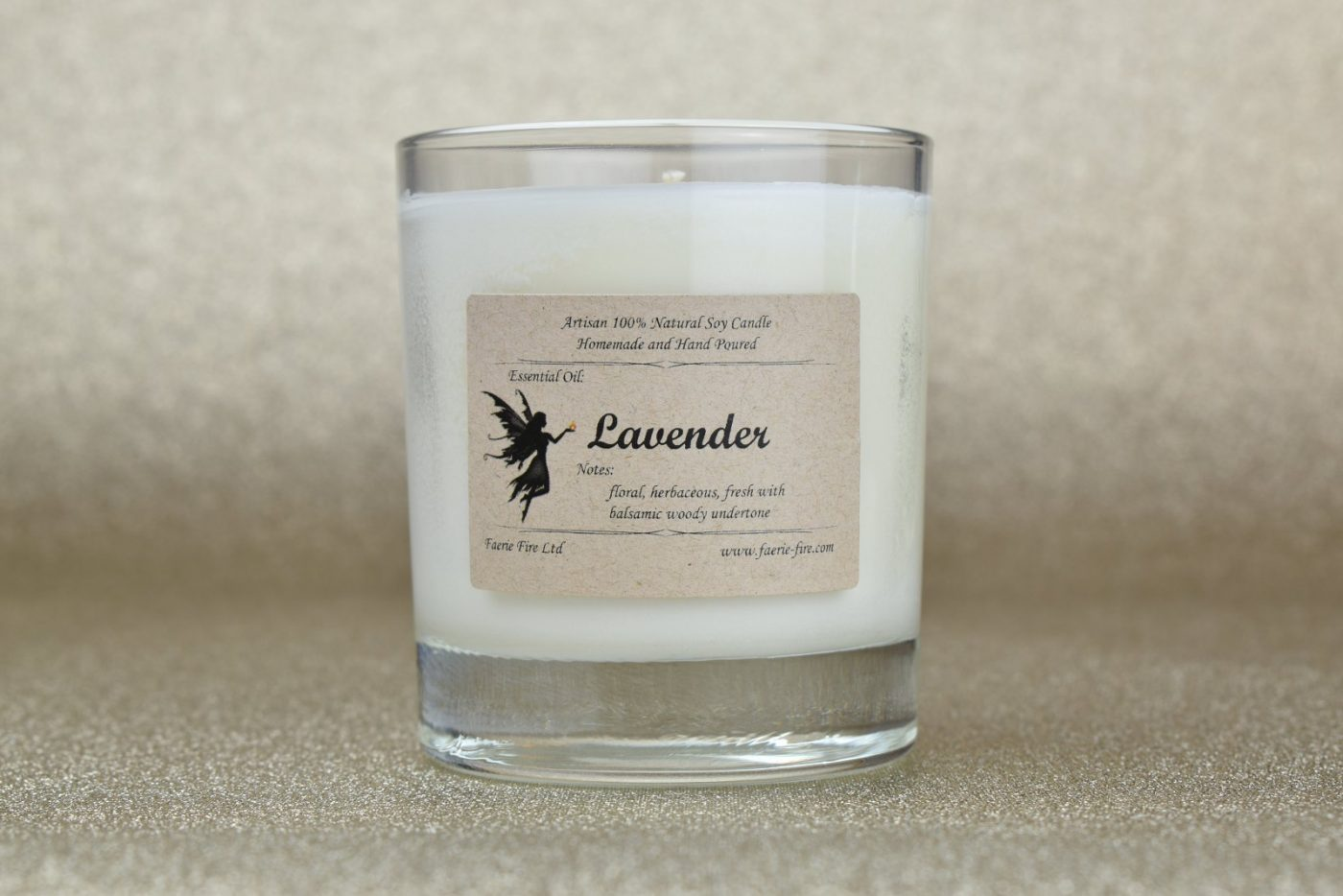 Lavender essential oil soy wax white candle in a clear glass jar against a gold plain background