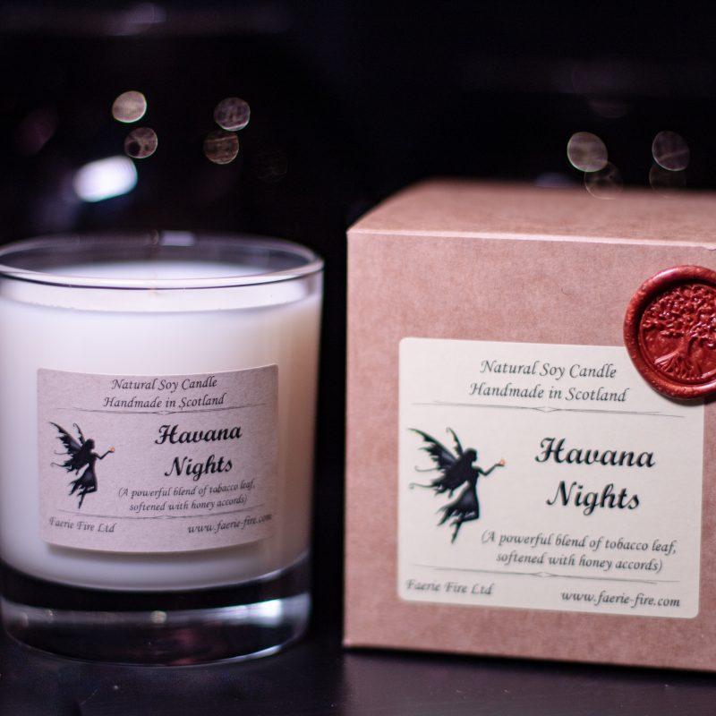 Havana nights dark honey and tobacco fragranced white candle in a clear glass jar alongside a presentation box sitting with a dark background