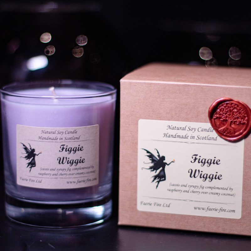 Purple candle in a glass jar called Figgie Wiggie which smells like cassis and fig, sitting next to a kraft gift box against a dark background