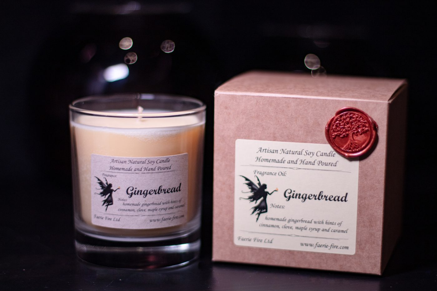 Pale yellow gingerbread fragranced candle in a clear glass jar beside a presentation box on a dark background