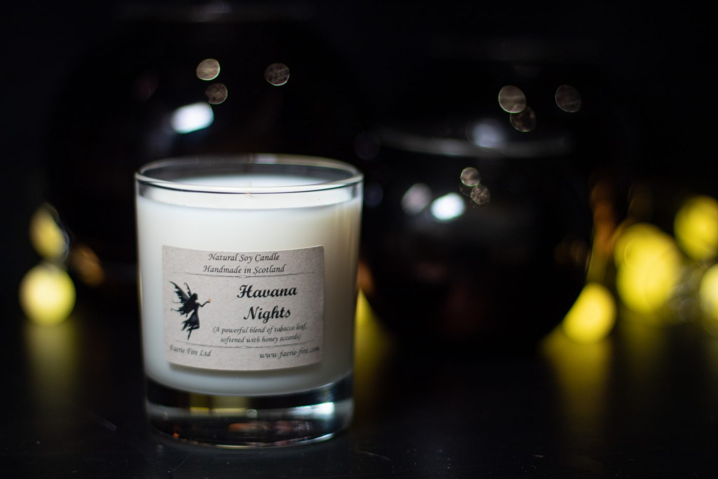 havana nights dark honey and tobacco jar candle sitting on a table with a dark background