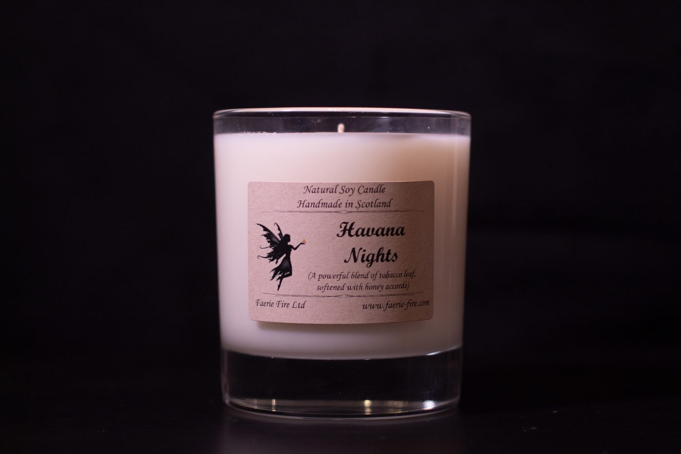 Havana nights honey and tobacco fragranced white jar candle in clear glass against a black background