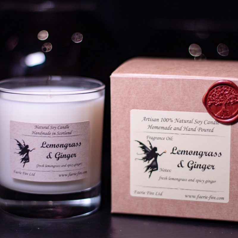 White soy candle in a clear glass jar smelling like lemongrass and ginger, sitting next to a brown presentaiton box against a dark background