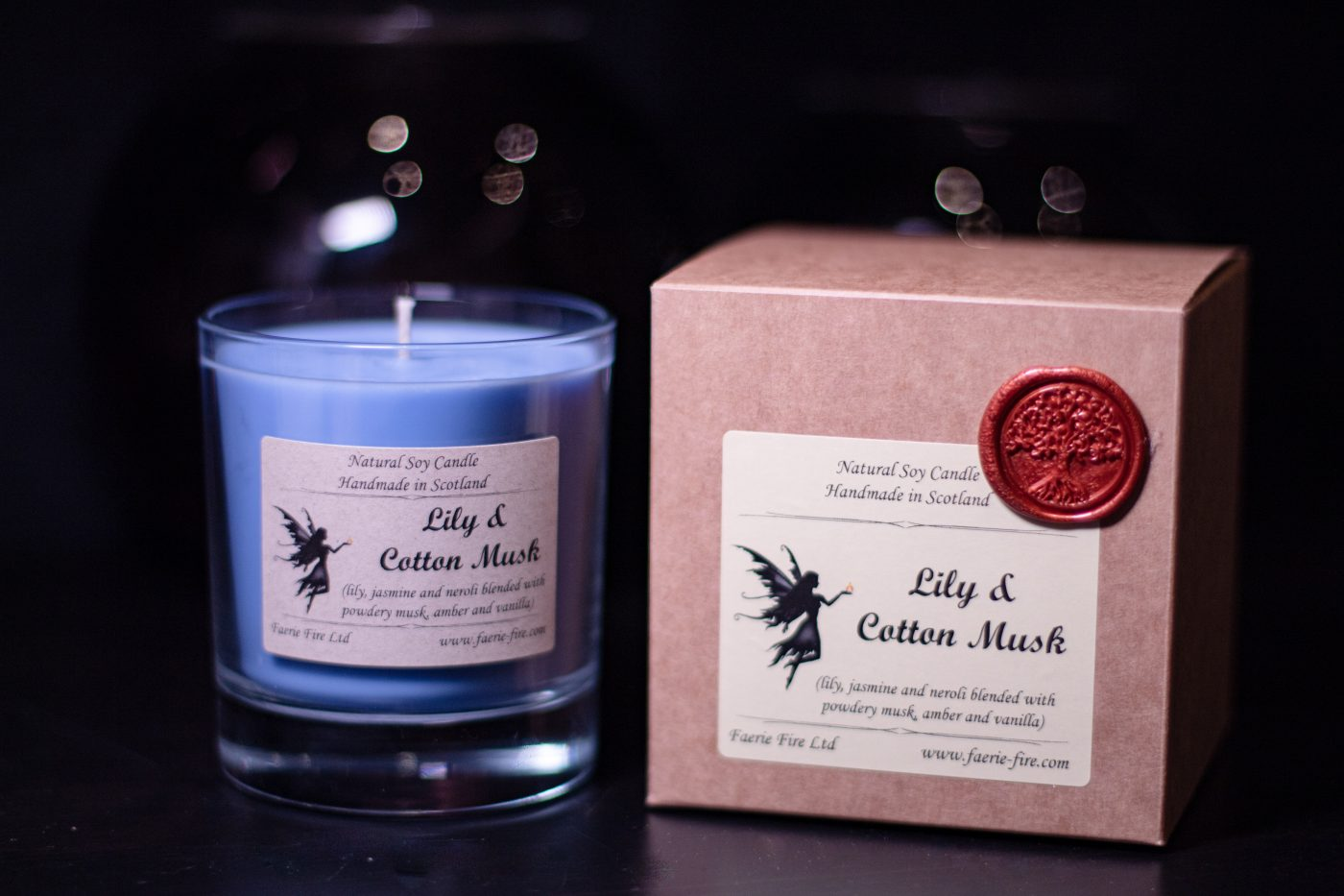 Blue soy wax candle in a clear glass jar, sitting next to a presentation box smelling like lily and cotton musk, against a dark background