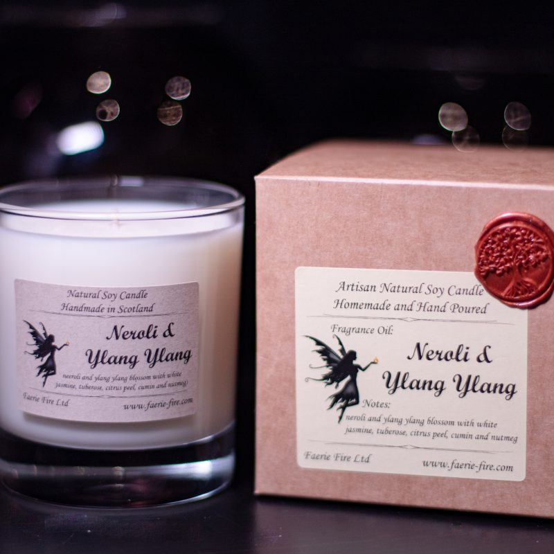 White neroli and ylang ylang soy candle in a glass jar beside a presentation box against a dark background