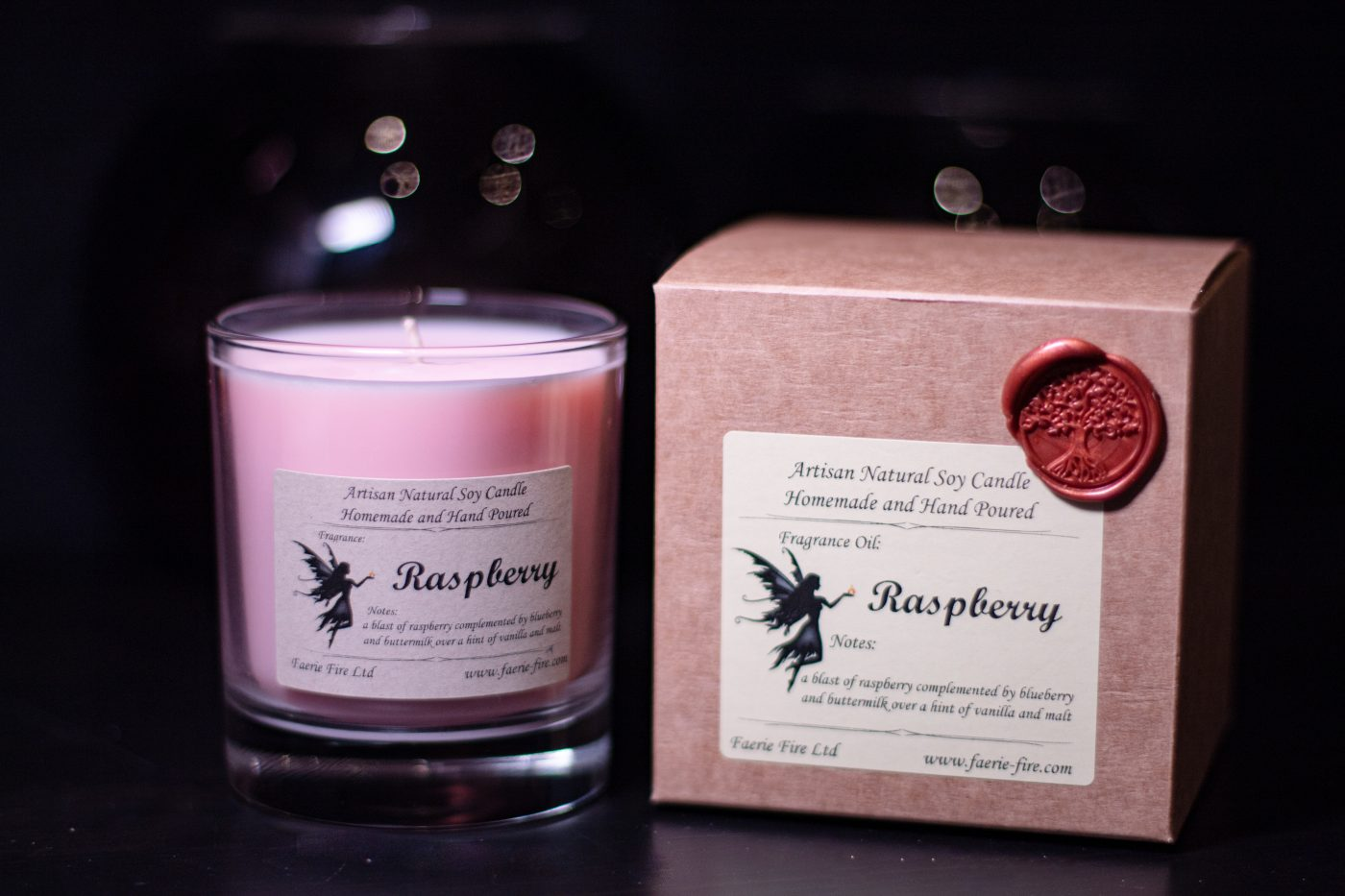 Raspberry pink soy wax candle in a clear glass beside a presentation box against a dark background