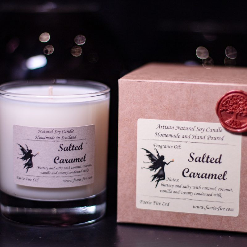 Salted caramel fragranced white soy wax candle in a clear glass jar beside a gift box against a dark background