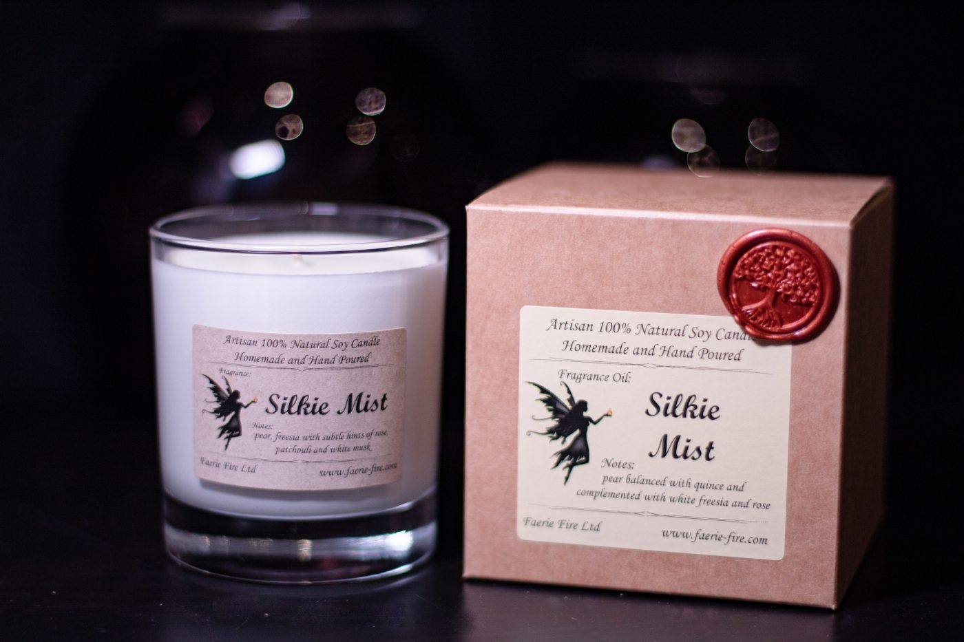Pale green silkie mist soy candle in a clear glass jar smelling like pear and freesia, beside a gift box against a dark background