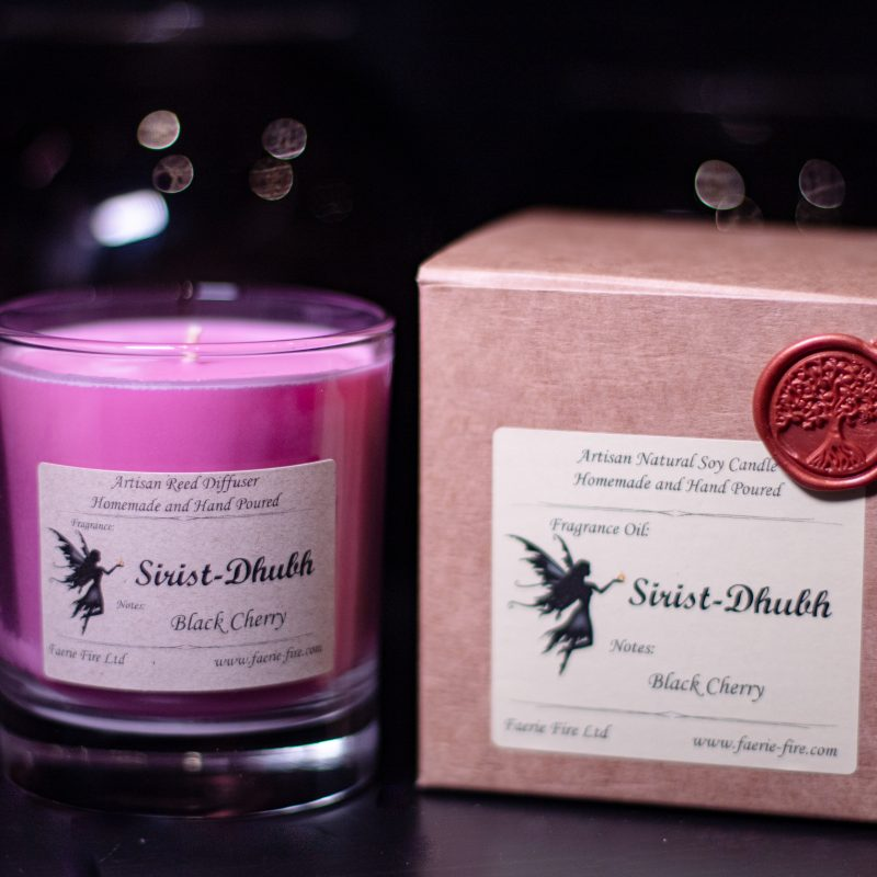 Pink black cherry fragranced soy candle in a clear glass jar beside a gift box against a dark background
