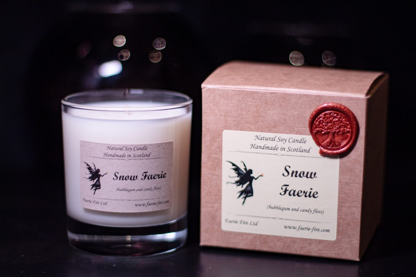 White snow faerie soy candle in a clear glass jar beside a gift box against a dark background smelling like pear drops
