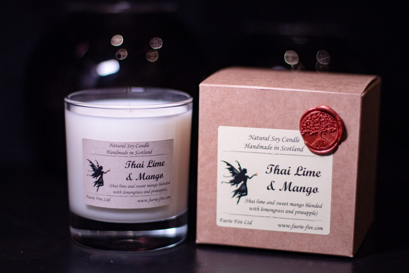 Thai lime and mango fragranced white soy vegan candle in a clear glass jar, beside a gift box on a dark background