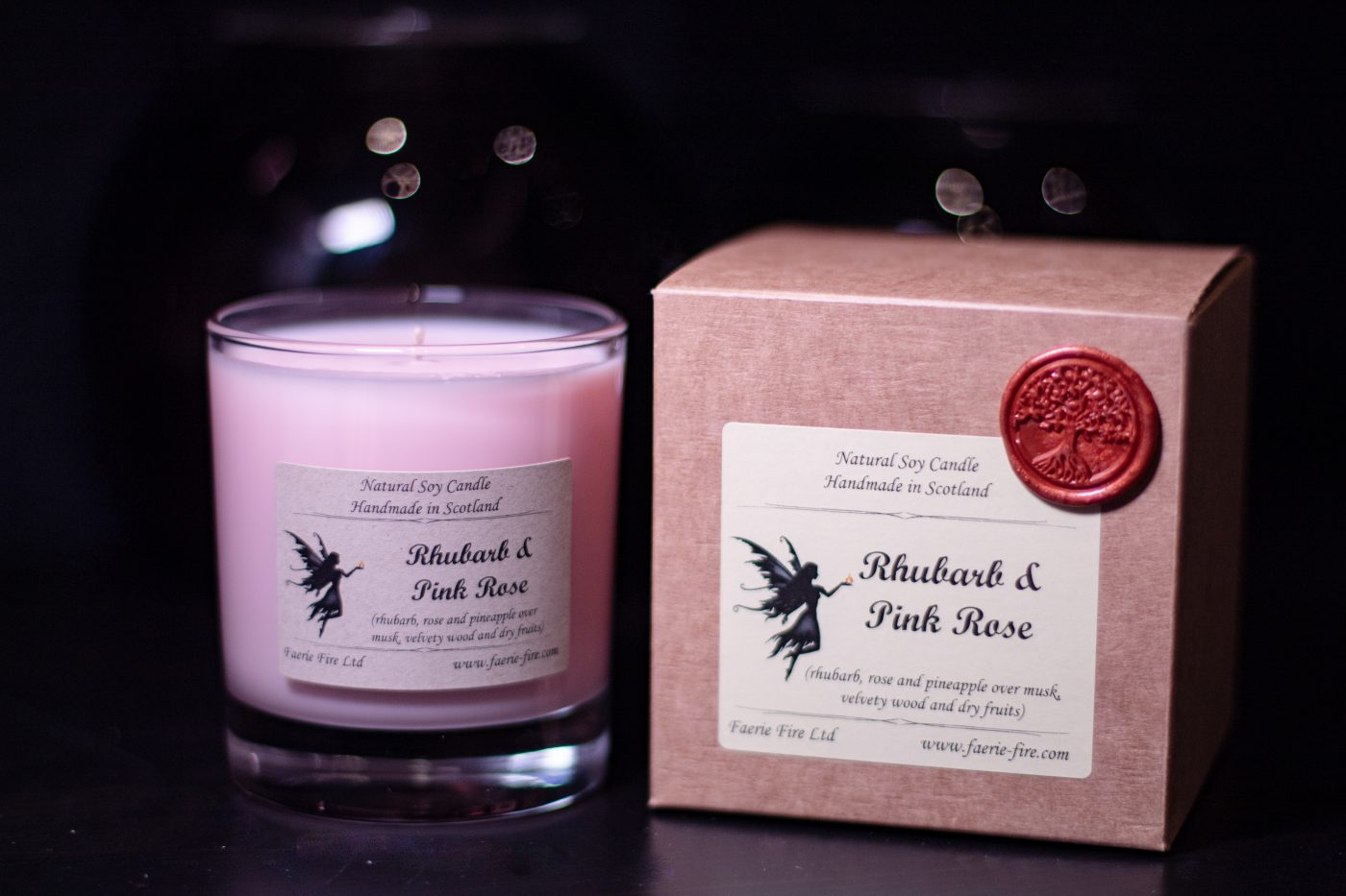 Rhubarb and rose fragranced pink candle in a clear glass jar beside a gift box against a dark background