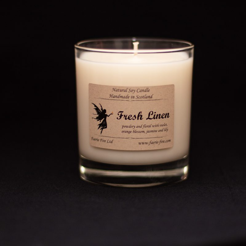Fresh Linen white candle in a clear glass against a black background. smelling like fresh linen or clean cotton
