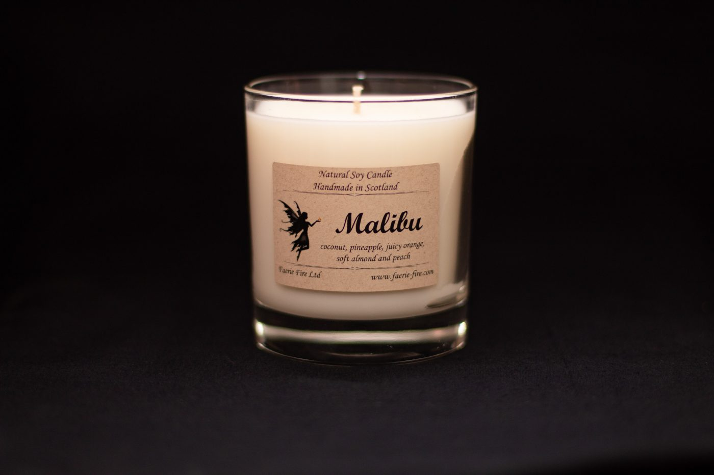 White soy candle in a clear glass jar smelling like coconut, pineapple and almond against a black darkground